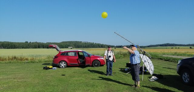 Henri OH3JR releasing a small balloon to assess the wind direction and speed. Martti OH1ON in the background. (photo by OH3EYZ)