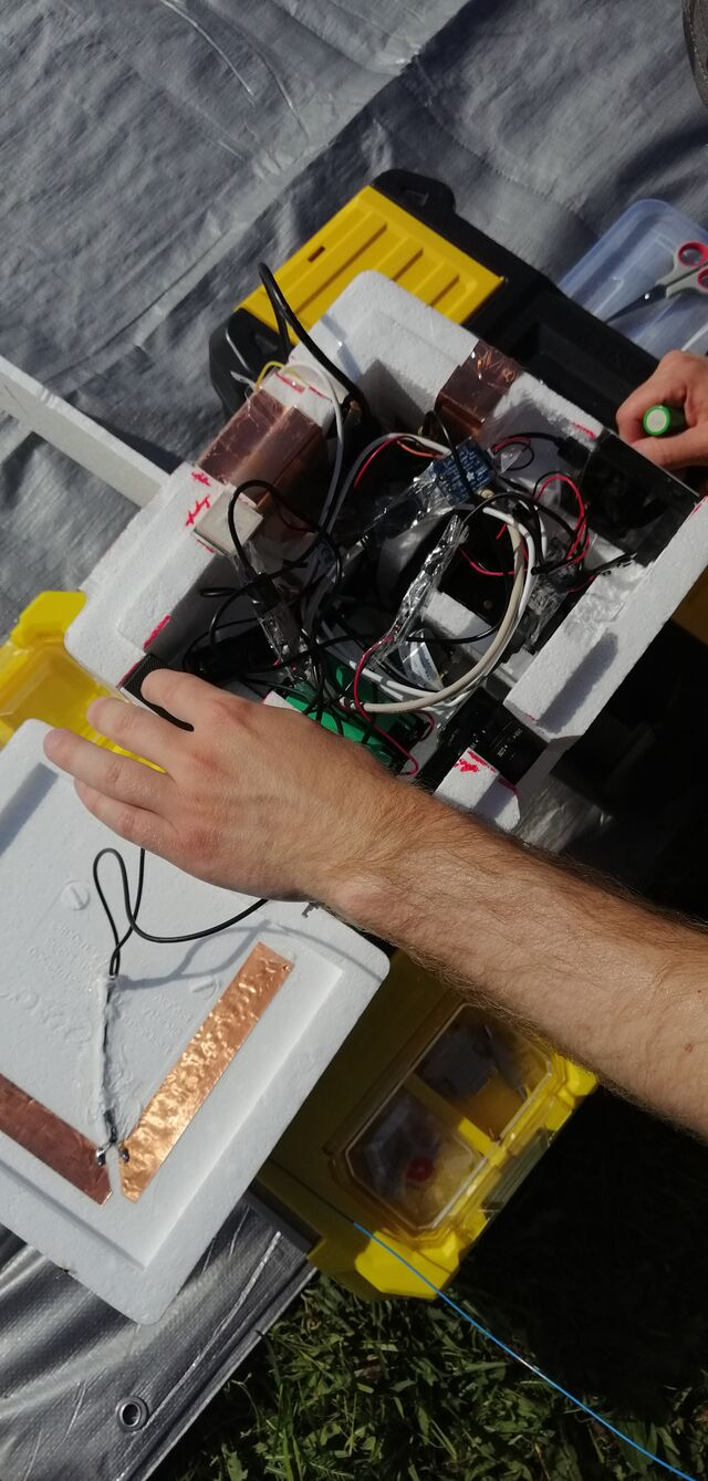 Mikael OH3BHX installing new batteries and powering on all the tracking equipment in the balloon payload. (photo by OH3EYZ)